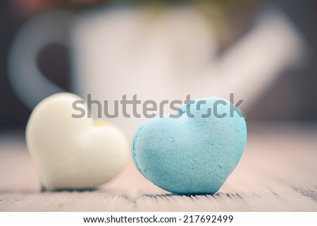 macarons in heart shape with flower on wood table,vintage tone style - stock photo