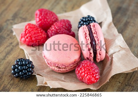 Macaroons and berry fruits on the table - stock photo