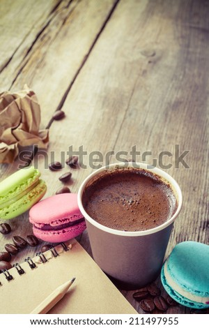 macaroons, espresso coffee cup and sketch book on wooden rustic table, vintage stylized photo - stock photo