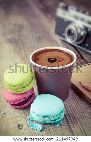 macaroons, espresso coffee cup, sketch book and retro camera on wooden rustic table, vintage stylized photo - stock photo