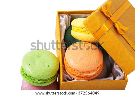 Macaroons in gold box isolated on white background.