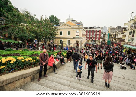 MACAU, CHINA - FEBRUARY 22, 2016:Many people walking and shopping at street infant of Ruins of St. Paul, It has many shops for Tourists to buy or eat. - stock photo