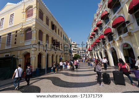 MACAU, CHINA - NOVEMBER 3, 2012: Tourists visit the Historic Center of Macau. Historic Center of Macau was inscribed on UNESCO World Heritage List in 2005. - stock photo