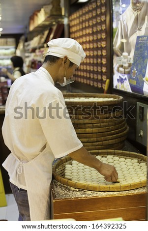 MACAU - OCTOBER 30: Confectioner manufactures biscuits in candy store on October 30, 2012 in Macau, China. Manufacture and sale of confectionery products is very popular business in Macau. - stock photo