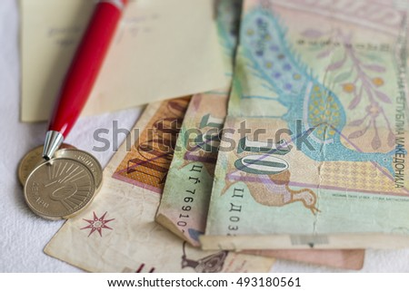 Macedonian money in paper and coins, piece of paper and red pen on white background