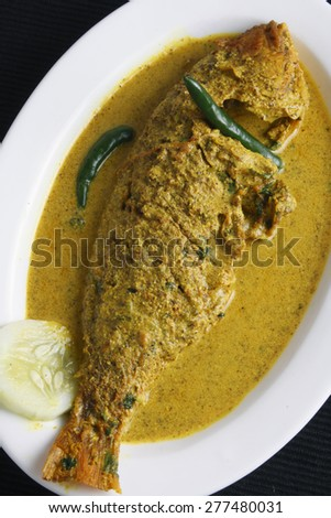 Macher jhol is a light fish or vegetable stew seasoned with ground spices like ginger, fried cumin powder, coriander, chilly and turmeric with pieces of fish and slices of vegetables. - stock photo
