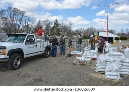 MACHESNEY PARK, IL - APRIL 20:High school students volunteer to help a flood victim load sandbags on to his pickup truck. April 20, 2013 Machesney Park, IL - stock photo