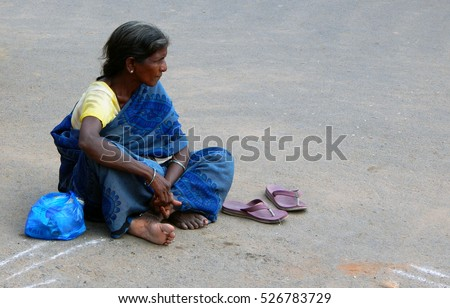 MACHILIPATNAM, INDIA-NOVEMBER 30:Indian senior homeless woman sit in front of Saibaba Temple seeking help and alms from visitors on November 30,2016 In Masula,India.