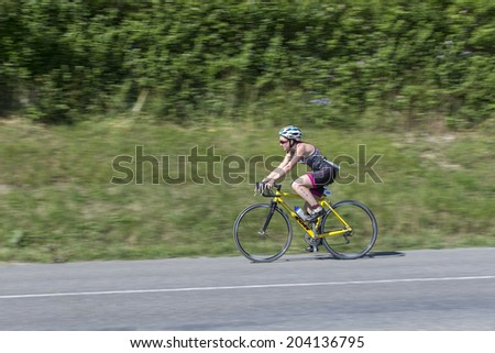 MACHILLY, FRANCE - JULY 6, 2014: Unidentified athlete participates in the cycling race of the Lake Machilly Triathlon which is part of the TriSaleve of Annemasse organization.