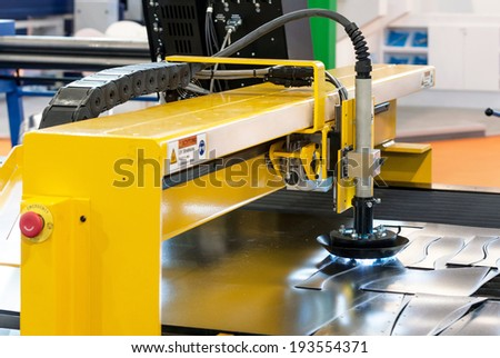 Machine cutting steel in a factory - stock photo