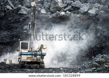 Machine drilling holes for demolition in Limestone Quarry - stock photo
