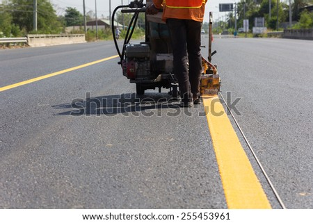 Machine eject and worker on road and traffic sign painting. - stock photo