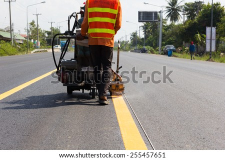 Machine eject and worker on road and traffic sign painting.