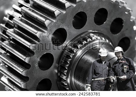machine engineers, workers with giant cogs and gears in the background - stock photo