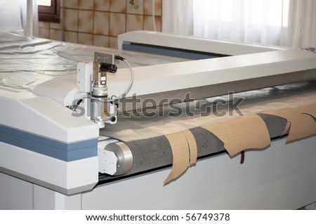 Machine for cutting a large variety of different products: carpet, composite, upholstery and PVC. Cutting technical textiles up to a working width of 3,4 m. - stock photo