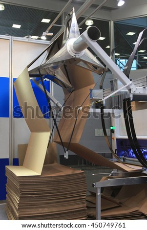 machine for cutting cardboard filing for cardboard boxes - stock photo