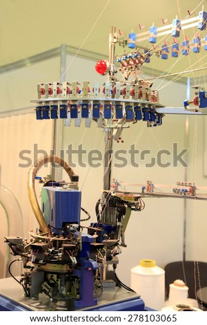 Machine for knitting socks at the textile factory - stock photo