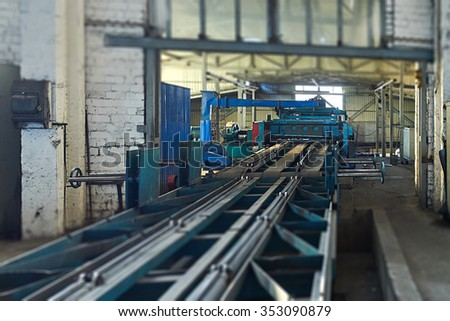machine for slitting steel sheet. Tilt-shift effect.