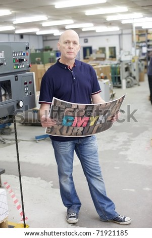 Machine minder standing next to a printing press - stock photo