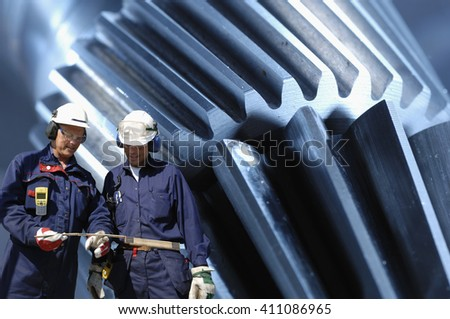 machine parts and engineering with two industry workers in foreground, cogwheels and gears - stock photo