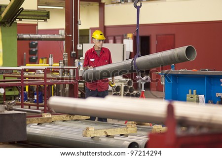 Machine shop worker checking for defects on metal tube - stock photo