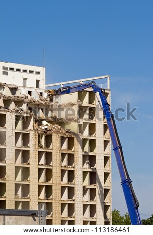 Machine taking down a large residential building