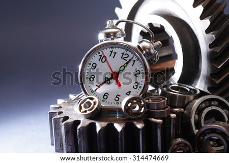 Machinery concept. Alarm clock on heap of old gears and ball bearings - stock photo