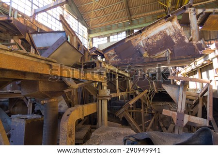 machinery destroyed in a coal mine abandoned after the war - stock photo