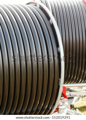 Machines, production concept. Detailed closeup of dark flexible plastic hose, pipes.
