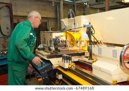 Machinist working a metal lathe - stock photo