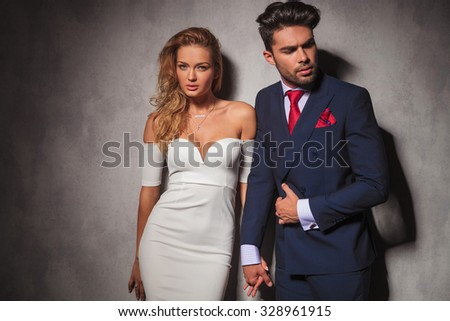 macho fashion elegant man holding his lover by her hand and looks to a side, sexy woman is looking at the camera in studio - stock photo