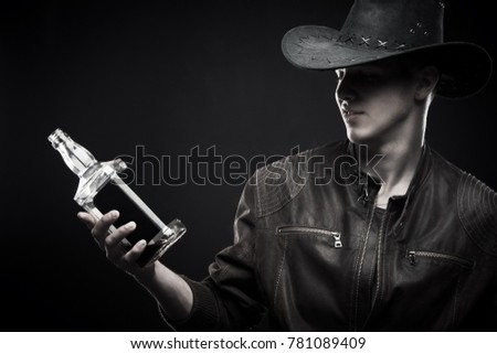 Macho in cowboy hat with bottle of whisky posing over dark background