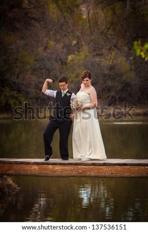Macho lesbian groom with bride on dock over pond - stock photo