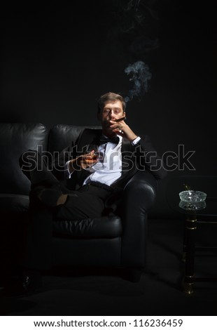Macho man in a stylish tuxedo sitting in the darkness at a nightclub puffing on a cigar and drinking brandy or cognac - stock photo