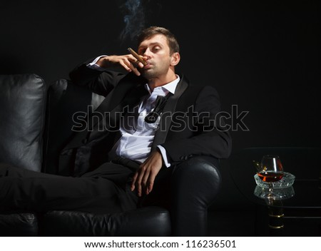 Macho man in a stylish tuxedo sitting in the darkness at a nightclub puffing on a cigar and drinking brandy or cognac