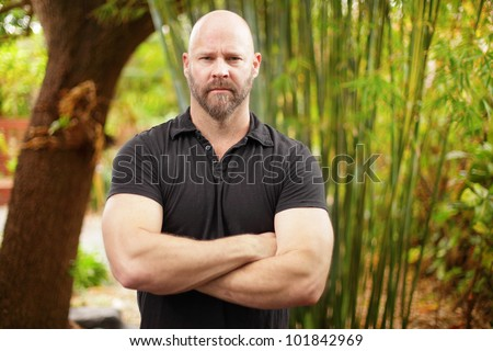 Macho man with arms crossed - stock photo