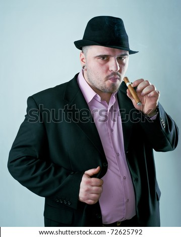 Macho man with cigar in black hat - stock photo