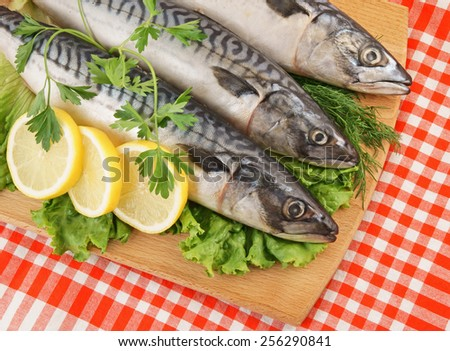 Mackerel fish with greens, lemon and wooden cutting board on red tablecloth - stock photo