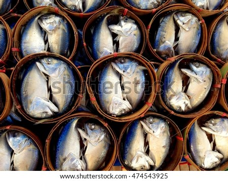 Mackerel in bamboo baskets on sale in the bazaar morning. And in the summer sun.