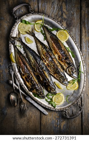 Mackerels served on silver plate with lemon - stock photo