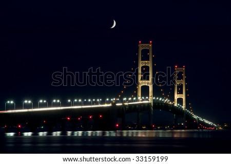Mackinac Bridge spanning the Upper and Lower Peninsula of Michigan. NIght shot with very dark sky and crescent moon. - stock photo