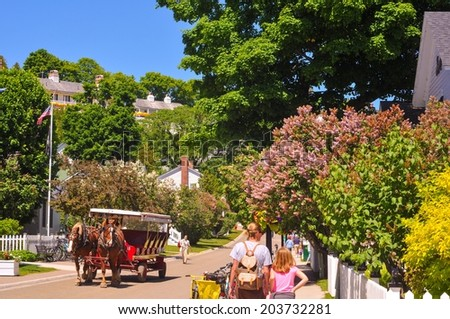 MACKINAC ISLAND, MI - JUNE 26, 2014: A horse-drawn cab and pedestrian visitors amble along flowery Market Street on a sunny summer day. - stock photo