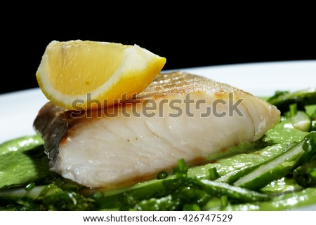 macro appetizing fish with vegetables in a white plate on a dark background