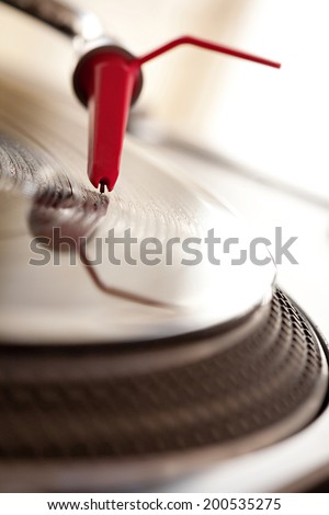 Macro close up detail view of a record player with a red needle touching the groove of a vinyl album playing music, interior. Still life professional musical equipment objects. - stock photo