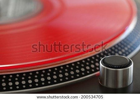 Macro close up detail view of a red vinyl album on a professional dj turntable, interior. Still life background of professional musical equipment objects. - stock photo