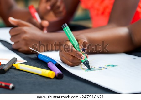 Macro close up of African kids hands drawing with wax crayons at desk. - stock photo