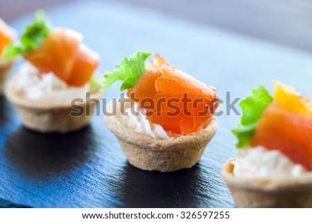 Macro close up of Appetizing Mini puff smoked salmon pastry tart lets for catering. - stock photo