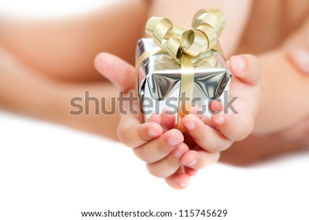 Macro close up of babies hands holding small present. Isolated. - stock photo