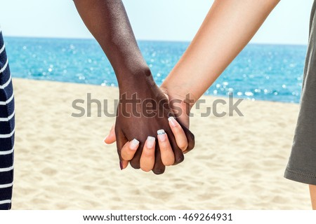Macro close up of diverse female hands holding against sea background.
