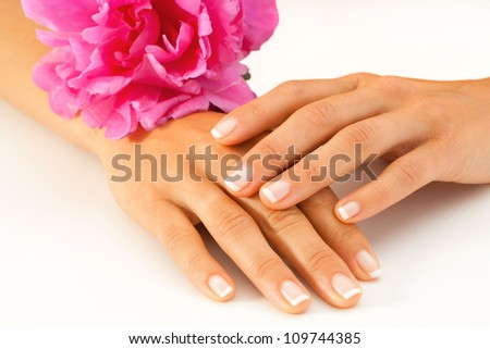 Macro close up of female hands with french manicure and pink decorative flower.